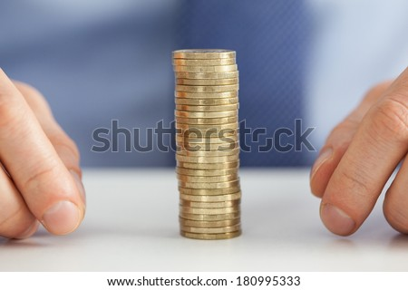 Businessman hands and stack of coins - closeup shot