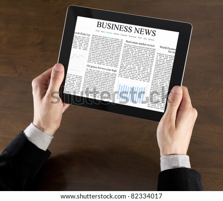 Businessman hands are holding the touch screen device with business news on screen - stock photo