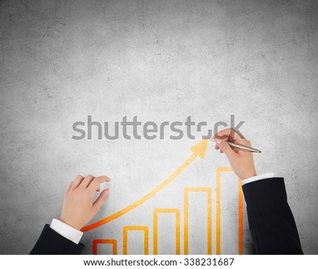 Businessman hands drawing with pen increasing arrow over concrete background
