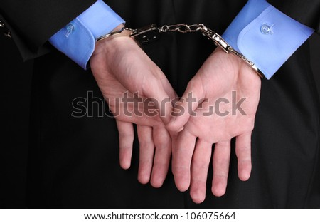 Businessman hands fettered with handcuffs - stock photo