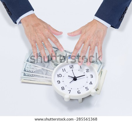 Businessman hands grabbing dollar money and clock - stock photo
