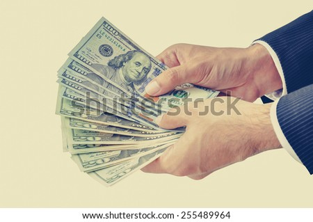 Businessman hands holding money, US dollars (USD) - vintage style color effect - stock photo