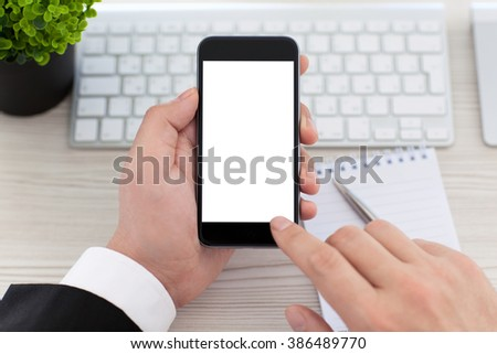 Businessman hands holding phone with isolated screen on the desk in the office - stock photo
