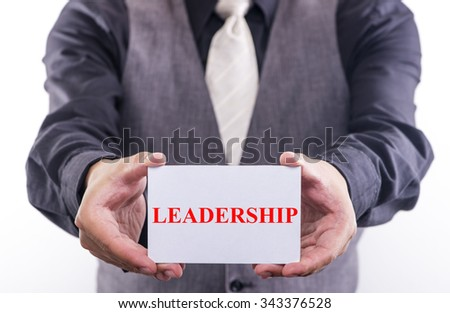 Businessman hands holding white card with leadership written - stock photo
