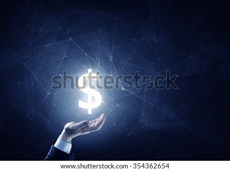 Businessman hands on dark background holding glowing dollar sign - stock photo