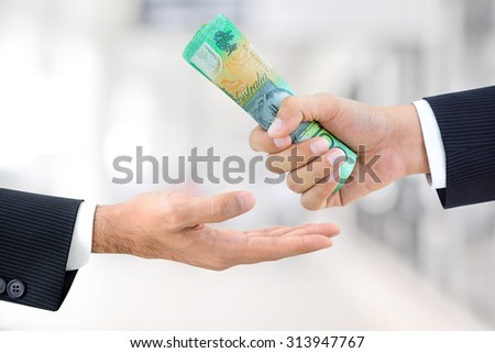 Businessman hands passing money, Australian dollar (AUD) banknotes, on white gray background
