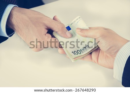 Businessman hands passing money, Euro currency (EUR), bribery concept - vintage tone - stock photo