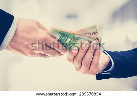 Businessman hands passing money, Euro currency (EUR), on white gray background - vintage tone - stock photo