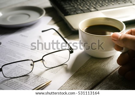 Businessman  hands working on laptop with coffee cup on table. vintage tone.