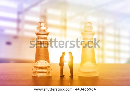 Businessman handshake for agreement with partnership to agree their business. King chess game - stock photo
