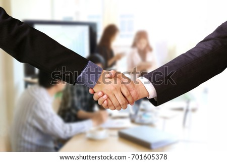 Businessman handshake for closing the deal with business people team in office background.