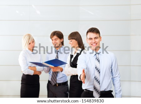 businessman handshake, hold hand shake welcome gesture, Handsome young excited business man happy smile at conference hall over group of businesspeople working background, people meeting - stock photo