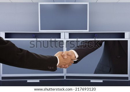 Businessman handshake on video conference screen - stock photo