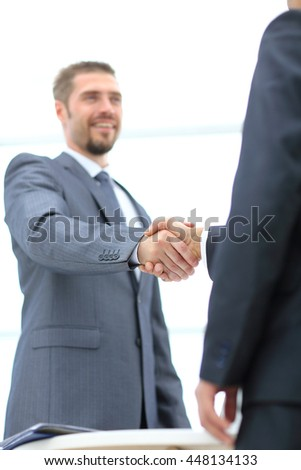 Businessman handshaking colleague in an office
