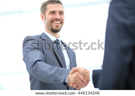 Businessman handshaking  in an  office - stock photo