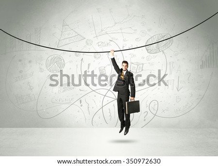 Businessman hanging on a rope with analysis and graphs background