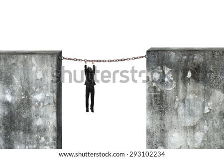 Businessman hanging on rusty chain connected two high dirty concrete walls, with white background. - stock photo