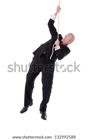 Businessman hanging onto a rope fearing from below isolated on white - stock photo