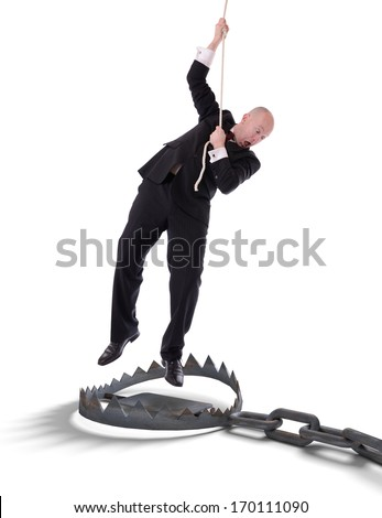 Businessman hanging onto a rope, fearing trap below, isolated on white - stock photo