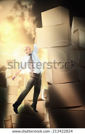 Businessman hanging over a cardboard box cliff - stock photo