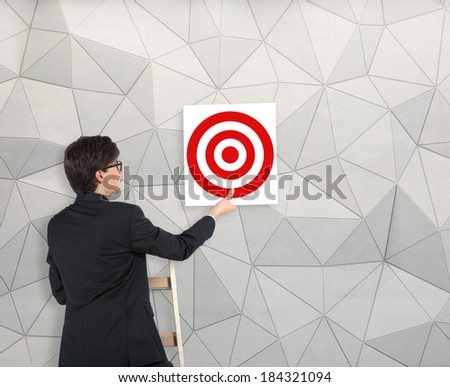 Businessman hanging up the target - stock photo