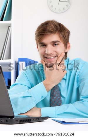 businessman happy smile sitting at the desk in office, handsome young business man wear blue shirt.