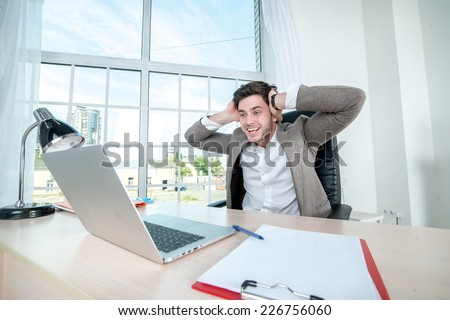 Businessman happy to work on a laptop. Young successful businessman holding his head with his hands and looking into laptop while sitting at a desk and a laptop in the office - stock photo