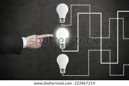 Businessman has chosen the most prospective idea among others. A finger is pointing out the light bulb.  - stock photo