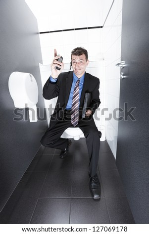 businessman having a conversation from the restroom