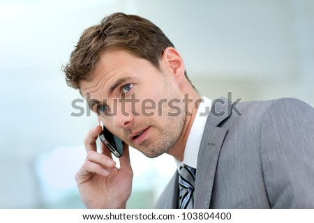 Businessman having a phonecall in building hallway - stock photo