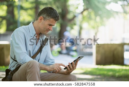 Businessman having a relaxing break at the park, he is sitting on a bench and using a digital tablet