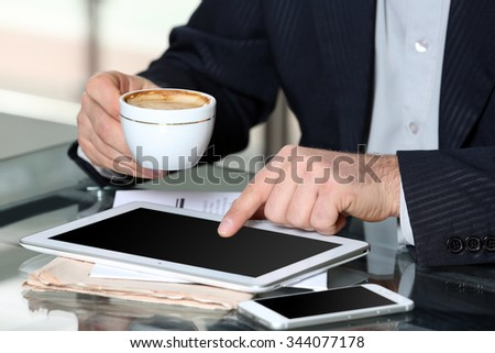 Businessman having lunch and working in a cafe, close-up - stock photo