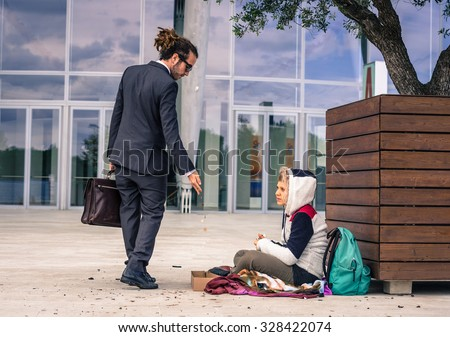 Businessman helps a homeless giving money - business, people and lifestyle concept - caucasian people - stock photo