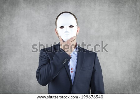 Businessman hidden behind the mask - stock photo