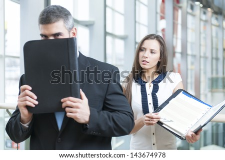 Businessman hides from coworker behind folder - stock photo