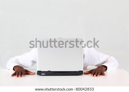 Businessman hiding behind laptop computer - stock photo