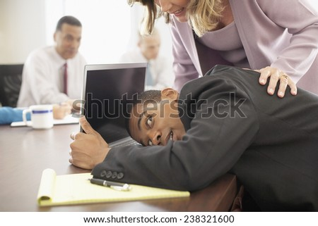 Businessman Hiding Behind Laptop in a Meeting - stock photo