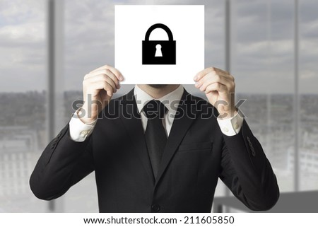 businessman hiding face behind sign lock symbol - stock photo