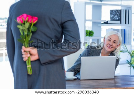 Businessman hiding flowers behind back for colleague in office - stock photo