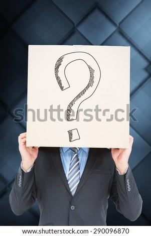 Businessman hiding head with a box against dark grey room - stock photo