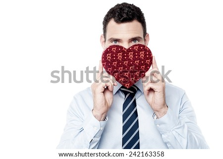 Businessman hiding his half face with heart shaped gift box - stock photo