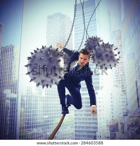 Businessman hindered by balls balanced on rope - stock photo