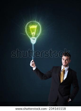 Businessman hold a shining idea bulb on a blue background - stock photo