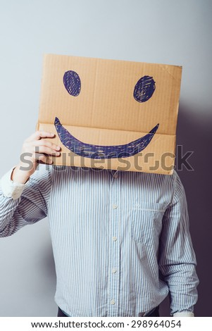 Businessman hold board with smile face emoticon on gray background - stock photo