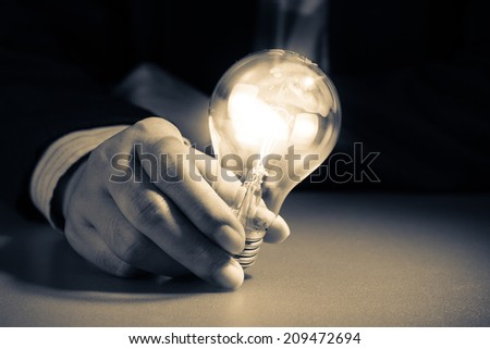 Businessman hold glowing light bulb in the darkness - stock photo
