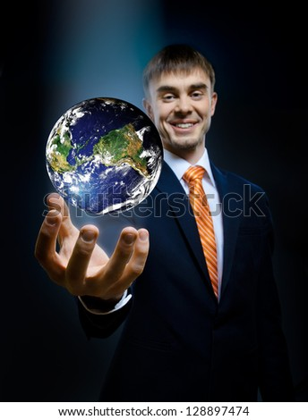 businessman hold in hand terrestrial globe,  blue background,  business concept image planet by: Stokli, Nelson, Hasler Laboratory for Atmospheres Goddard Space Flight Center www.rsd.gsfc.nasa.gov/rsd