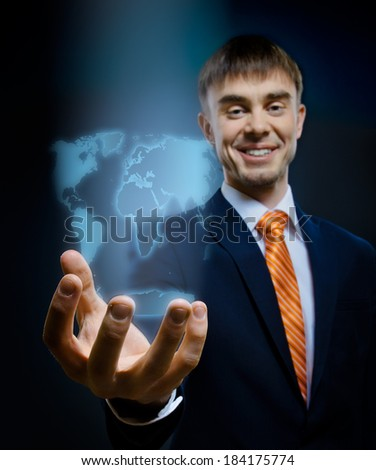businessman hold in hand terrestrial globe, on dark blue background,  business concept - stock photo