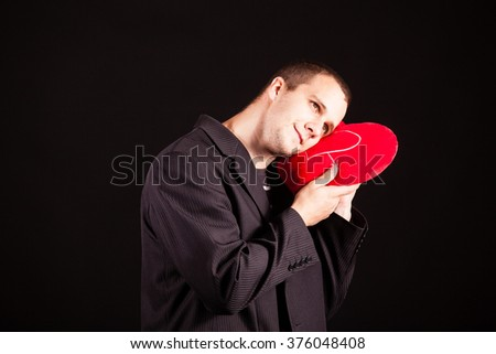 businessman hold red heart pillow - stock photo