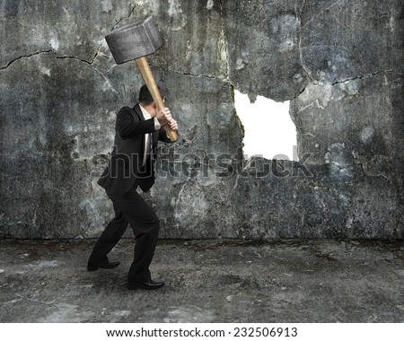 businessman hold sledgehammer cracking big white hole on concrete wall background