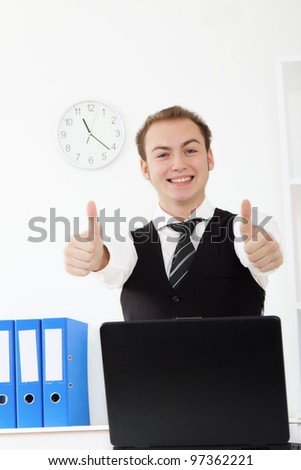 businessman hold thumb up gesture, happy smile at the desk in office, handsome young business man, looking at camera